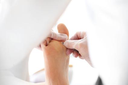 Podologia. Lekarz  usuwa skalpelem odcisk na stopie
