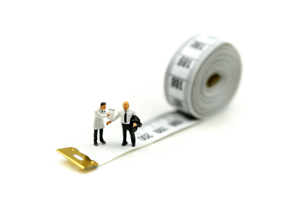 Miniature people : Doctor and patient with tape Measure,Healthcare and diet concept.