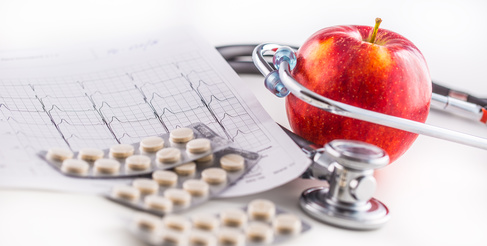 Stethoscope apple and pills on white background.