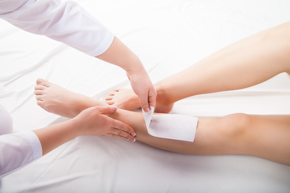 Beautician waxing  woman legs in a spa salon